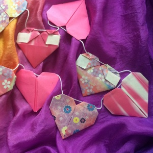 To make a paper heart garland, glue or tape string to the underside of the last flaps that were folded down before finishing.