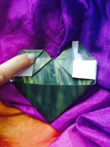 Fold the tips of the triangles at the top down to meet the crease.