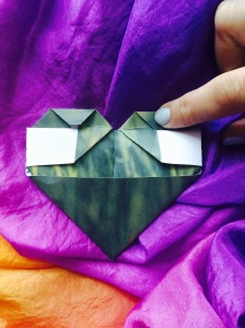 Fold the opposite tip of the triangle to meet the middle crease.